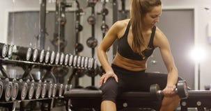 A mulher saudável e focsued levanta peso no gym da aptidão vídeos de arquivo