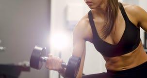 A mulher saudável e focsued levanta peso no gym da aptidão filme