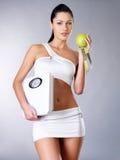 A mulher saudável está com as escalas e a maçã verde. Fotos de Stock