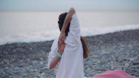 A mulher saudável faz a ioga no mar no verão vídeos de arquivo