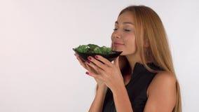 Mulher saudável feliz que aprecia o cheiro da salada deliciosa fresca filme