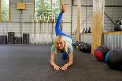 Mulher saudável nova magro dos esportes que faz o exercício o do pontapé do asno imagens de stock