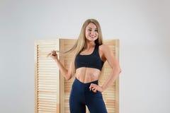 Mulher saudável nova no levantamento do sportswear Menina bonita feliz que sorri na câmera imagem de stock