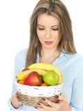 Mulher saudável nova que guarda uma cesta fresca do fruto Imagens de Stock Royalty Free