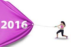 A mulher saudável puxa os números 2016 com bandeira Fotografia de Stock Royalty Free