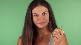 Mulher saudável que escolhe a maçã verde sobre a barra de chocolate imagem de stock