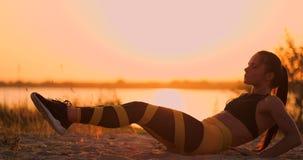 Mulher saud?vel apta que estica na esteira da ioga no beira-mar da praia, fazendo tritura??es do exerc?cio, o treinamento e o est vídeos de arquivo