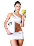 A mulher saudável está com as escalas e a maçã verde. Imagem de Stock