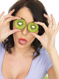 Mulher saudável nova que guarda Kiwi Fruit Pulling Expression maduro fresco Imagem de Stock