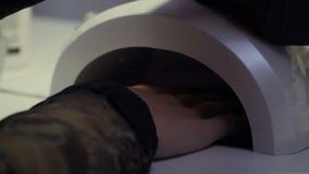 A mulher seca seu tratamento de mãos na Uv-lâmpada filme