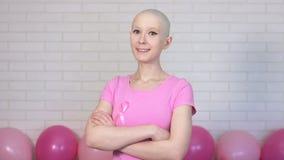 Mulher segura do sobrevivente do câncer da mama que olha cruzes seus braços que olham a câmera e que sorriem - câncer da mama video estoque