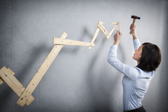 Mulher segura que constrói o gráfico positivo da tendência com martelo à disposição Imagem de Stock Royalty Free