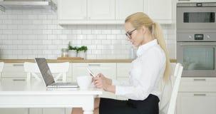 Mulher segura que trabalha em casa video estoque