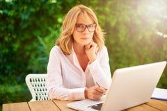 Mulher segura que usa o portátil no jardim fotos de stock