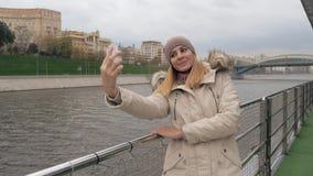 Mulher Selfie em Smartphone que está na terraplenagem de opiniões do rio e da cidade filme