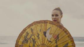 Mulher sensual do encanto no biquini preto com guarda-chuva chinês em uma praia vídeos de arquivo