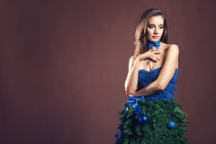 Mulher sensual no vestido da árvore de Natal no fundo marrom Imagens de Stock