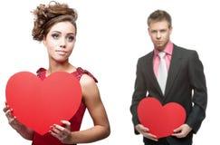 Mulher sensual nova e homem considerável que guardam o coração vermelho no branco Fotografia de Stock Royalty Free
