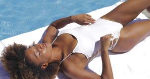 Mulher sensual nova que relaxa na piscina vídeos de arquivo