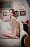 Mulher sensual nova que senta-se no sofá que relaxa Menina longa bonita do cabelo com roupa confortável que sonha acordado no sof Fotografia de Stock Royalty Free