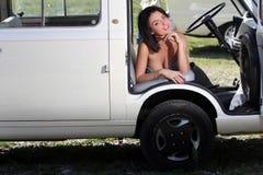 Mulher sensual que senta o carro retro imagem de stock