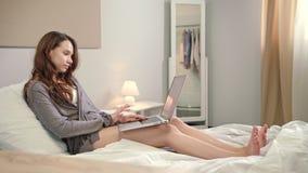 Mulher sensual que usa o laptop na cama Menina do estudante que procura em linha filme