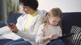 A mulher sent-se-ar no sof? e toc-se-ar na tela do telefone quando crian?a que usa o port?til para jogar video estoque