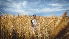 A mulher senta-se em um campo de trigo e aprecia-se a natureza Fotos de Stock Royalty Free