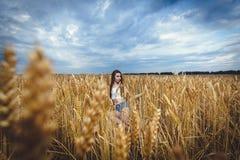 A mulher senta-se em um campo de trigo e aprecia-se a natureza Fotos de Stock