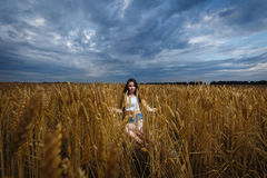 A mulher senta-se em um campo de trigo e aprecia-se a natureza Imagens de Stock