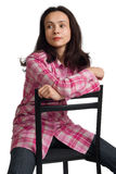 A mulher senta-se em uma cadeira de volta à parte dianteira. Imagem de Stock Royalty Free