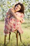 A mulher senta-se em uma cadeira em um jardim da mola Imagem de Stock Royalty Free