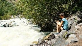A mulher senta-se em uma pedra e em olhares nos córregos de roda de um rio da montanha que corre ao longo da floresta, movimento  filme