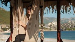 A mulher senta-se em uma rede em uma praia ensolarada e olha-se na distância vídeos de arquivo
