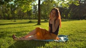 A mulher senta-se na grama verde e tem-se a conversação através do selfphone vídeos de arquivo