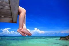 A mulher senta-se na ponte de madeira sobre o mar bonito Fotografia de Stock