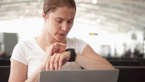 A mulher senta-se na sala de espera do aeroporto com portátil Mensagem ocasional da ordem da mulher de negócios no relógio espert filme