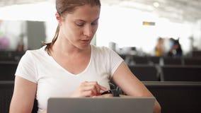 A mulher senta-se na sala de espera do aeroporto com portátil A mulher de negócios ocasional envia a mensagem no relógio esperto vídeos de arquivo