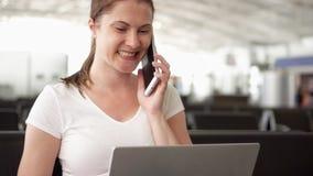 A mulher senta-se na sala de espera do aeroporto com portátil Mulher de negócios ocasional que fala no móbil com colega video estoque