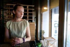 A mulher senta-se na tabela e na espera Imagem de Stock Royalty Free