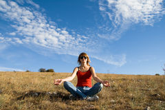 A mulher senta-se na terra e meditate Foto de Stock Royalty Free