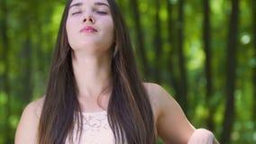 A mulher senta-se no banco com olhos fechados que escuta a natureza, sentindo a unidade do oneness filme