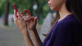 A mulher senta-se no banco e smartphone da utilização Vista próxima filme