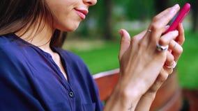 A mulher senta-se no banco e smartphone da utilização Vista próxima vídeos de arquivo
