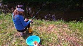 A mulher senta-se no coto perto da lagoa, relógio que joga o gato com peixes pequenos video estoque