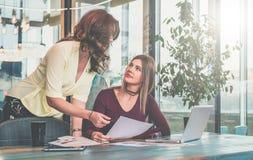 A mulher senta-se no escritório na tabela na frente do computador e guarda-se originais em sua mão, em segundo está estando ao la imagens de stock