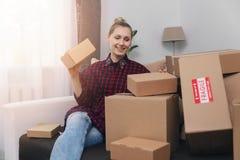 A mulher senta-se no sofá em casa com lote de caixas de cartão imagem de stock