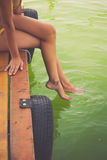 A mulher senta-se nos pés refrigerando da doca de madeira na água clara Foto de Stock Royalty Free