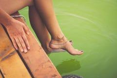 A mulher senta-se nos pés refrigerando da doca de madeira na água clara Fotografia de Stock Royalty Free