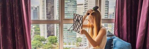 A mulher senta-se pela janela e usa-se uma BANDEIRA eletrônica da escova de cabelo, FORMATO LONGO fotografia de stock royalty free
